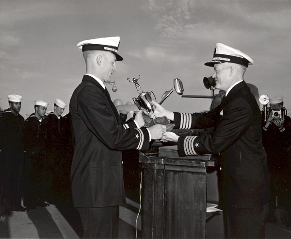 Ens J.W. Pieper accepts football trophy from the CO